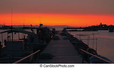 Evening scene of quay. Pier, boats and orange sky - Evening...
