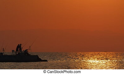 Evening scene of sea and fishermen on the pier - Slow motion...