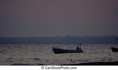 Evening scene of sea with moored boat rocking on waves -...