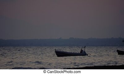 Evening scene of sea with moored boat rocking on waves