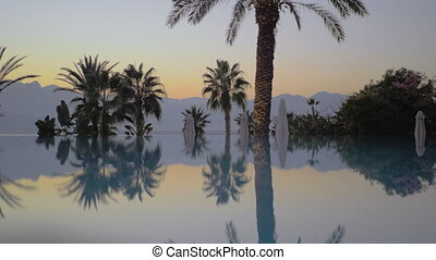 Evening scene on resort. Swimming pool, palms and mountains
