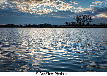 Evening sky over calm lake and reflection of clouds in waves