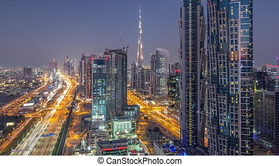 Evening skyline with modern skyscrapers and traffic on sheikh zayed road day to night timelapse in Dubai, UAE.
