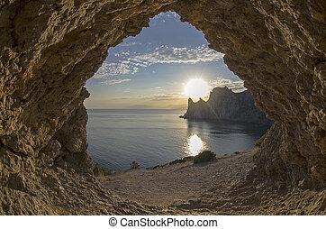 Evening sun setting behind the coastal cliffs. Crimea.