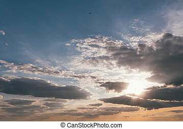 Evening sunset sky with bright rays of the sun and beautiful clouds