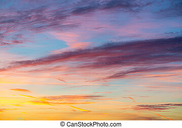 Evening sunset sky with bright rays of the sun and beautiful colorful clouds