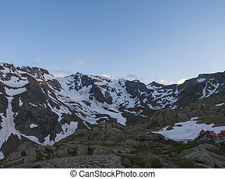 Evening sunset summer view of Bremer Hutte, terrace with snow-capped moutain peaks, Stubai Alps, Tyrol, Austria