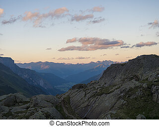 Evening sunset summer view of Stubai valley from Bremer Hutte at hiking trail, Stubai Hohenweg, rock, boulders and moutain peaks. Tyrol Alps, Austria