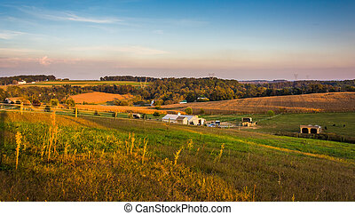 Evening view of farm fields and rolling hills in rural Lancaster County, Pennsylvania.
