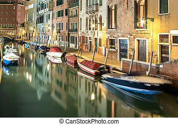 Evening view of illuminated old architecture, floating boats and light reflections in canals water in Venice, Italy.