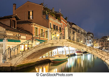 Evening view of illuminated old buildings, bridges, floating boats and light reflections in canals water in Venice, Italy.