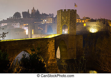 evening view of medieval bridge over river at Besalu. ...