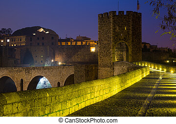 Evening view of medieval stone bridge with gate. Besalu - ...