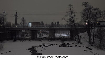 Evening view of passenger train running across the bridge in winter city