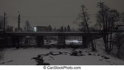 Evening view of passenger train running across the bridge in winter city