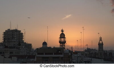 Evening view of Valencia and flying plane in the sky, Spain