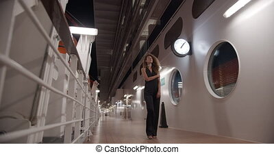 Evening walk of a beautiful girl in evening dress on the deck of a cruise ship.