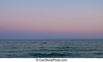 Evening waterscape with lonely boat rocking on sea waves