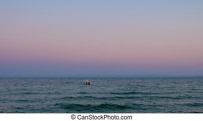 Evening waterscape with lonely boat rocking on sea waves -...