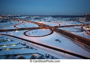 evening winter cityscape with big interchange, lighting columns and garages
