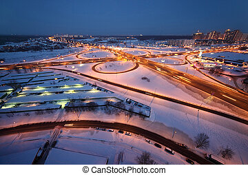 evening winter cityscape with big interchange and lighting columns