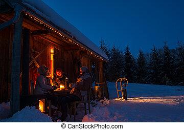 Evening winter cottage friends enjoy hot drinks in snow ...