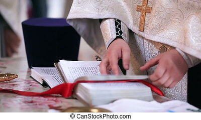 Evensong Bible - Priest holding an open Bible and praying