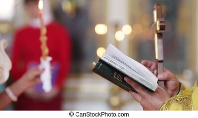 Evensoning Bible Pray - Priest holding an open Bible and...