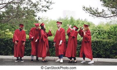 event., remise de diplomes, lent, groupe, danse, étudiants, mortar-boards, campus, mouvement, célébrer, multi-ethnique, dehors, robes, jour, rire
