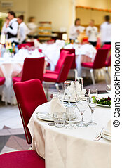 Events preparation for dinner, table appointment, unrecognizable waiters on background