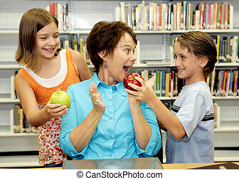 Everybodys Favorite Teacher - Two students giving apples to...