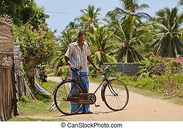 Man with old bicycle in a village in Sri Lanka.