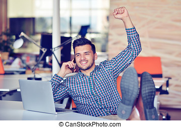 Cheerful young man in casual wear keeping arms raised and looking happy while sitting at the desk in office