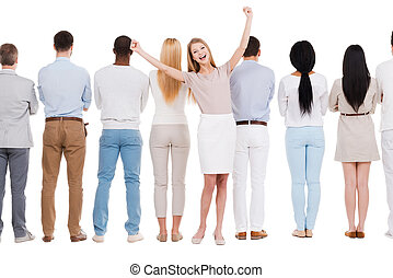 Everyday winner. Rear view of group of people standing in a row and against white background while one woman standing face to camera and expressing positivity