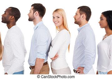 everyone, vontade, adquira, um, chance., vista lateral, de, bonito, mulher jovem, olhando câmera, e, sorrindo, enquanto, ficar, uma fileira, com, outro, pessoas, e, contra, fundo branco