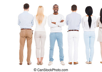 Everyone will get a chance. Rear view of group of people standing in a row and against white background while one cheerful African man standing face to camera and smiling