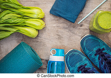 Everything for sports turquoise, blue shades on a wooden background and spinach smoothies. Yoga mat, sport shoes sportswear and bottle of water. Concept healthy lifestyle, sport and diet. Sport equipment. Copy space