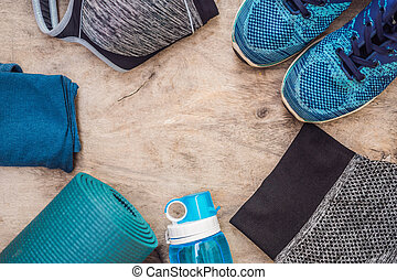 Everything for sports turquoise, blue shades on a wooden background. Yoga mat, sport shoes sportswear and bottle of water. Concept healthy lifestyle, sport and diet. Sport equipment. Copy space