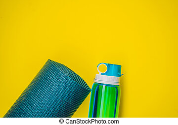 Everything for sports turquoise, blue shades on a yellow background. Yoga mat, sport shoes sportswear and bottle of water. Concept healthy lifestyle, sport and diet. Sport equipment. Copy space