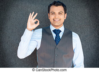Closeup portrait of young handsome happy, smiling excited man giving OK sign with fingers, isolated gray background. Positive human emotions, facial expressions, feelings, symbols, body language