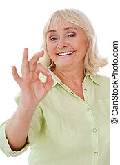 Everything is ok! Happy senior woman gesturing ok sing and smiling while standing isolated on white background