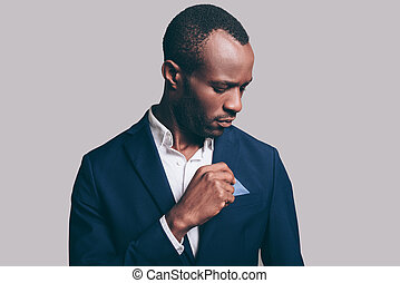 Everything should be perfect. Portrait of confident young African man adjusting his smart casual jacket while standing against grey background