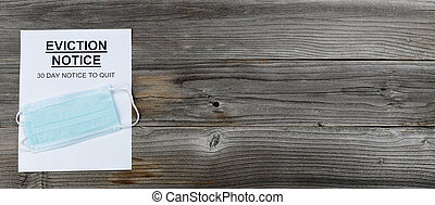 Eviction notice with personal facemask on rustic wooden table in flat lay format