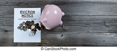 Eviction notice with toppled piggy bank spilling change on rustic wooden table in flat lay format
