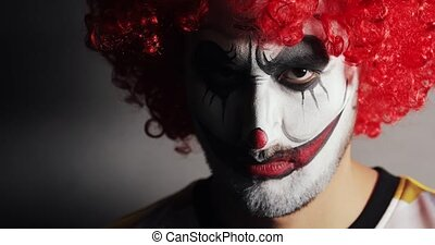 Evil angry face with makup of scary clown looks at camera in...