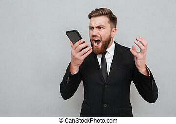 Evil bearded man in suit screaming in his smartphone