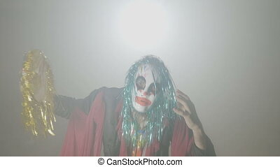 Evil clown coming out from smoke taking his mask off and...