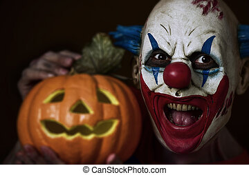evil clown with a carved pumpkin - closeup of a scary evil...