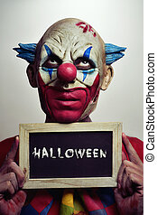 evil clown with a chalkboard with the word Halloween