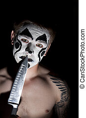 Evil clown with a knife - pumped up young man with tattoos...
